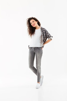Full length happy curly woman posing   over white wall