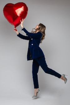 Full length of happy lady in suit holding heart shaped balloon and looking at it, on grey.