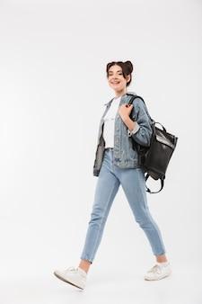 Полная длина счастливая студентка с двойной булочкой прическа в джинсовой одежде и рюкзаке гуляет с улыбкой, изолированная на белом