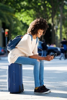 Полная длина счастливый путешественник, сидя на чемодан, проведение мобильный телефон в парке