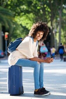 Полная длина счастливый путешественник, сидя на чемодан, проведение смартфон в парке