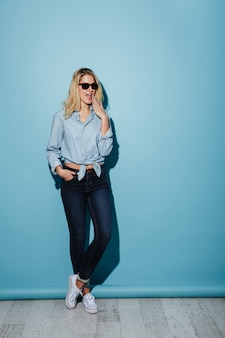 Full length happy woman in shirt and sunglasses