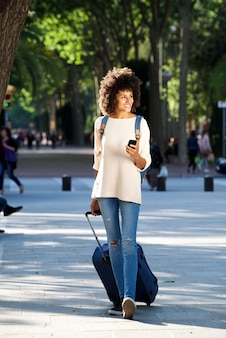 Full length happy woman walking in park with suitcase and mobile phone
