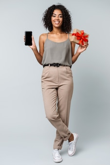 Full length of a happy young african woman casually dressed standing isolated, holding blank screen mobile phone, showing gift box