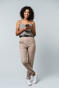 Full length of a happy young african woman casually dressed standing isolated, holding mobile phone
