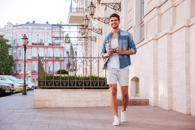 Full length of happy young man with photo camera walking on the street