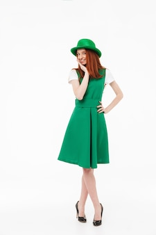 Full length of a happy young redheaded girl wearing green hat, celebrating st patricks's day isolated over white wall, posing