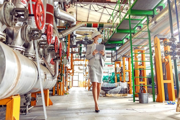 Full length of hardworking blond female supervisor in suit with helmet and face mask on holding tablet and walking around heating plant during corona virus outbreak.