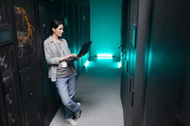 Полноразмерный портрет женщины-инженера по данным с высоким углом обзора, держащей ноутбук во время работы с суперкомпьютером в серверной комнате, копировальное пространство