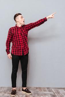 Полнометражный битник в красной рубашке, указывая и глядя в сторону. изолированный серый фон