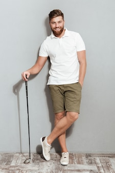 Full length image of a bearded man posing with club