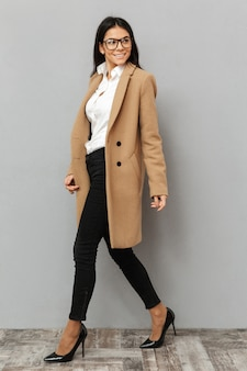 Full length image of beautiful woman wearing glasses and beige coat walking on heels and looking aside with smile, isolated over gray background