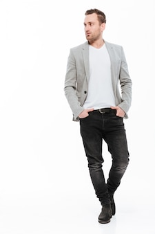 Full-length image of brunette businessman in jacket confidently posing with hands in pockets and looking aside, isolated over white wall