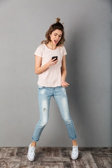 Full length image of carefree woman in t-shirt listening music from smartphone with earphones while jumping over grey
