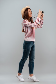 Full length image of cheerful asian woman in sweater