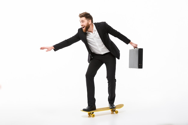 Full length image of cheerful bearded business man with briefcase