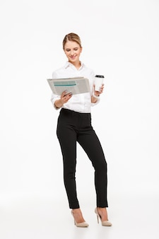 Full length image of cheerful blonde business woman reading newspaper while holding cup of coffee over white wall