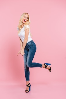 Full length image of cheerful blonde woman posing in studio and looking away over pink