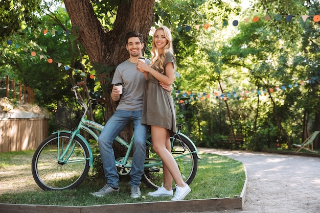 Full length image of cheerful lovely young couple posing together near bicycle and looking at the camera with coffee outdoors