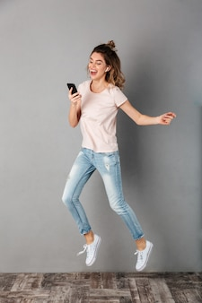 Full length image of cheerful woman in t-shirt listening music from smartphone with earphones while jumping and having fun over grey