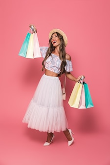 Full length image of cheerful young woman wearing straw hat and fluffy skirt smiling and holding colorful paper shopping packages