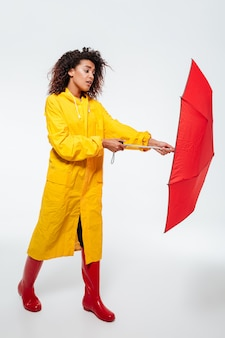 Full-length image of confused african woman in raincoat opening umbrella