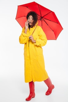 Full length image of confused african woman in raincoat