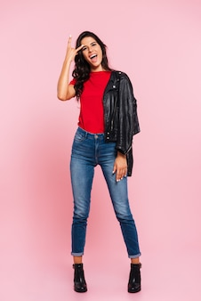 Full length image of cool screaming brunette woman showing rock gesture and looking at the camera over pink
