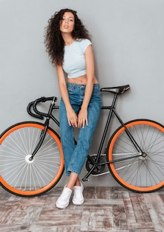 Full length image of curly pretty woman posing with bicycle and looking at the camera over gray background