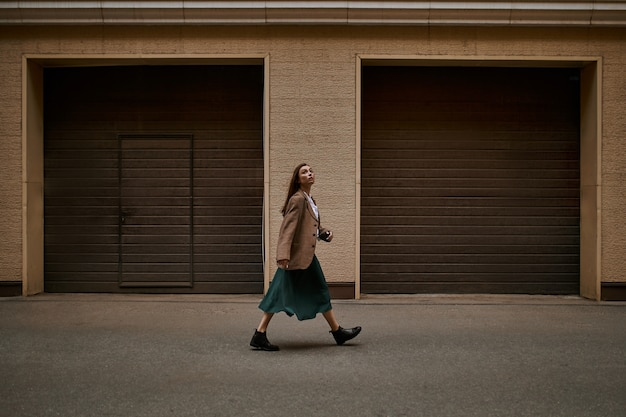 Immagine a figura intera di giovane donna alla moda con i capelli larghi che esce contro le porte delle tapparelle, va a lavorare, ha un'espressione facciale seria