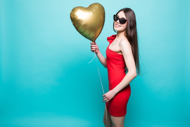Full-length image of gorgeous woman in fancy red outfit posing with heart shape ballon, isolated over green wall