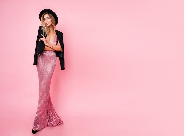Full length image of graceful sexy blonde woman in sequin maxi dress and stylish black hat posing on pink wall. amazing figure. height heels. shopping. fashionable look.