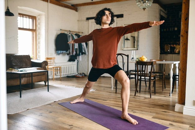 Full length image of handsome young male with strong athletic body practicing yoga indoors, standing in warrior 2 pose or virabhadrasana, taking deep breaths.