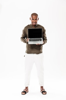 Full length image of happy african man showing blank laptop computer screen and looking