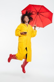 Full length image of happy african woman in raincoat hiding under umbrella and jumping while listening music  white