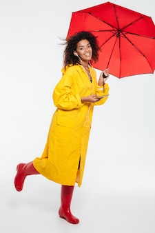 Full length image of happy african woman in raincoat hiding under umbrella and listening music over white