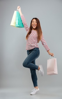 Full length image of happy asian woman in sweater rejoice