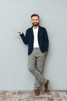 Full length image of happy bearded man in busines clothes with arm in pocket holding copyspace on the pound and looking at the camera over gray