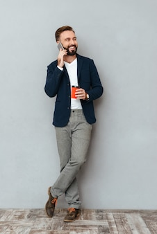 Full length image of happy bearded man in business clothes