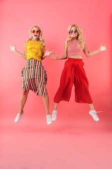 Full length image of happy blonde twins in sunglasses jumping and  over pink wall
