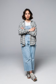 Immagine integrale della donna castana felice che posa con le braccia incrociate e lo sguardo