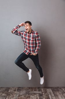 Full length image of happy man in shirt and jeans jimping and looking away with arm in pocket