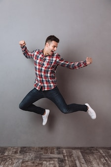 Full length image of happy man in shirt and jeans jumping
