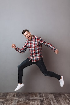 Full length image of happy man in shirt and jeans screaming while running and looking