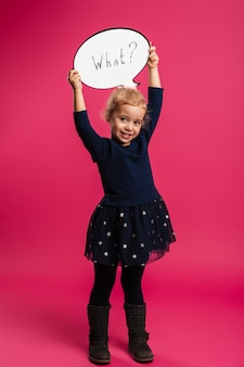 Full length image of happy young blonde girl holding speech bubble what and looking at the camera over pink wall