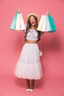 Full length image of joyful woman wearing straw hat and fluffy skirt shouting and holding colorful paper shopping packages