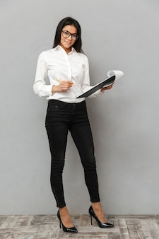 Full length image of lovely woman wearing businesslike outfit and glasses holding clipboard and writing down notes in papers, isolated over gray background