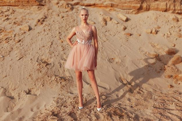 Полнометражное изображение привлекательной блондинки, позирующей в платье с вышивкой, позирующей в пустыне, глядя на камеру.