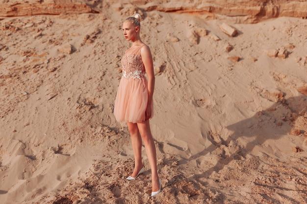 Полнометражное изображение красивой блондинки, позирующей в платье с вышивкой на пустыне, стоя на песке.