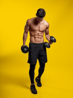 Изображение в полный рост молодого человека, уверенно сидящего на тренировке портрета без рубашки с гантелями
